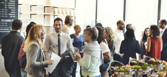 Event planners Calgary talks about - group of colleagues mingle at a corporate gathering